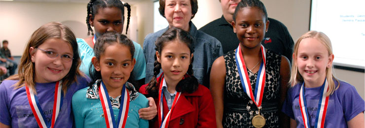 A group of students pose for a photo with their medals on