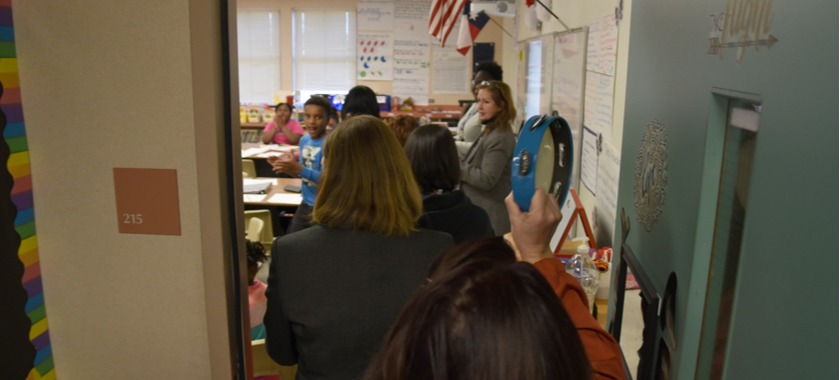 Delcua looks at the group as they walk into the classroom to surprise her.