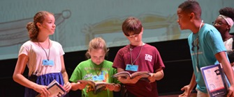 Students on a stage reading from a script during a play rehearsal.