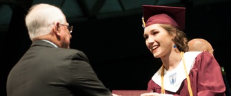 Board of Trustee member handing a female Killeen High School graduate her diploma on graduation day.